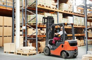warehouse worker driver in uniform loading cardboard boxes by fo